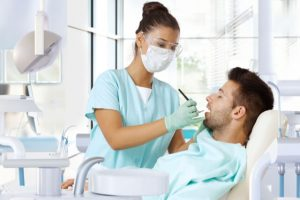 The dentist performs dental cleaning on the patient.