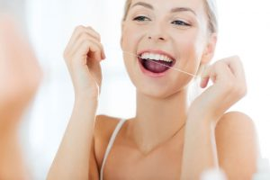 The young woman uses dental floss to clean her teeth.